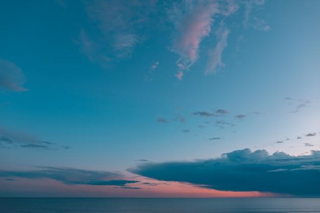 Puesta de sol con nubes y cielo azul turquesa y naranja con el mar