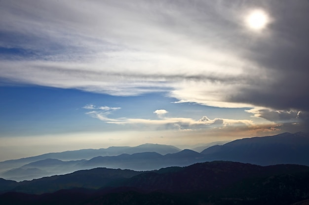 Puesta de sol en las nubes sobre un fondo de montaña