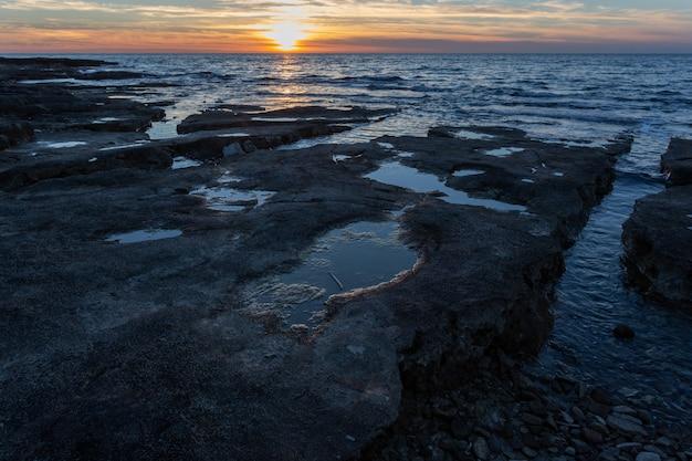 Puesta de sol en la orilla con formaciones rocosas en el mar adriático en savudrija, istria, croacia