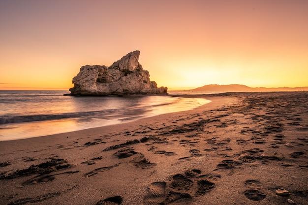 Puesta de sol en la playa de crow's rock, málaga, españa.
