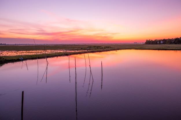Puesta del sol reflejada en el lago reservorio huay saneng, surin, tailandia.