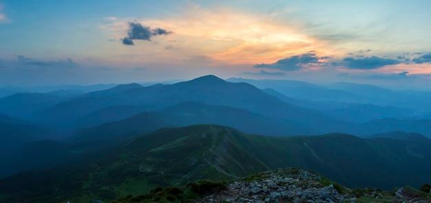 Puesta de sol sobre la cresta verde de la montaña cubierta de niebla azul densa