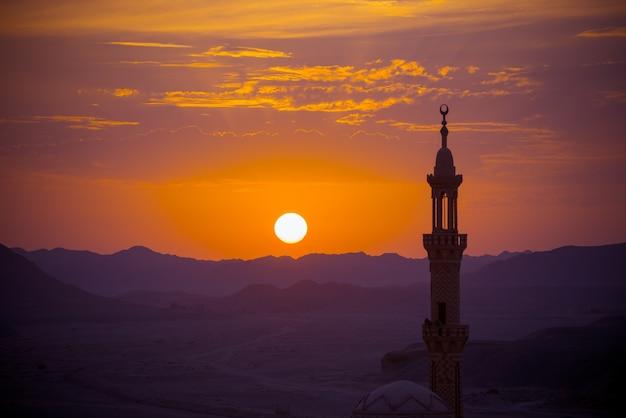 Puesta de sol sobre el desierto con mezquita musulmana en primer plano