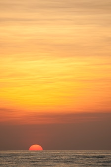 Puesta de sol sobre el mar en calma con un brillo naranja