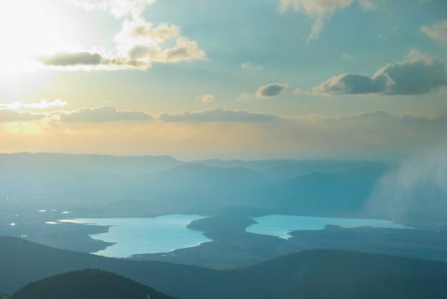 Puesta de sol sobre el paisaje del lago con colinas, nubes y cielo