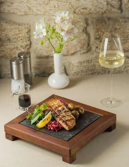 Puesto de comida de madera con filete de pescado a la plancha y verduras