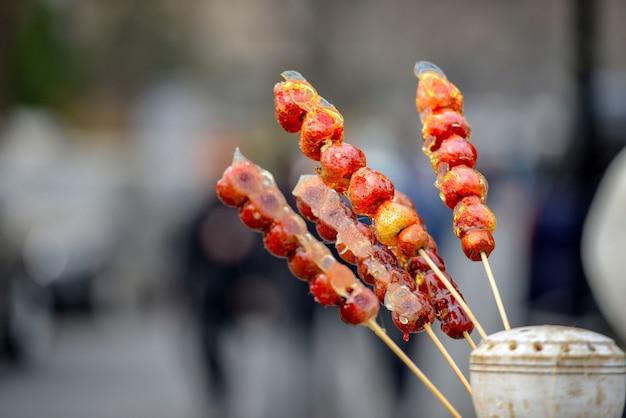 Puesto con fruta caramelizada en palo en la calle qianmen en la ciudad de beijing