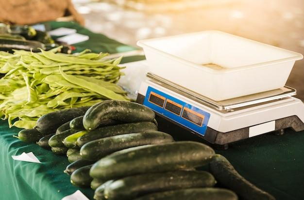 Puesto de mercado con escala de peso y vegetales orgánicos en mesa.