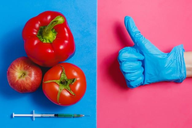 Pulgar arriba líquido verde en jeringa, tomate rojo, manzana, pimienta.