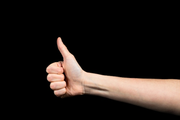 Pulgar arriba de mano mujer caucásica sobre fondo negro