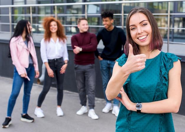 Pulgar que muestra femenino sonriente joven encima del gesto que mira la cámara mientras que sus amigos que se colocan empañan el fondo