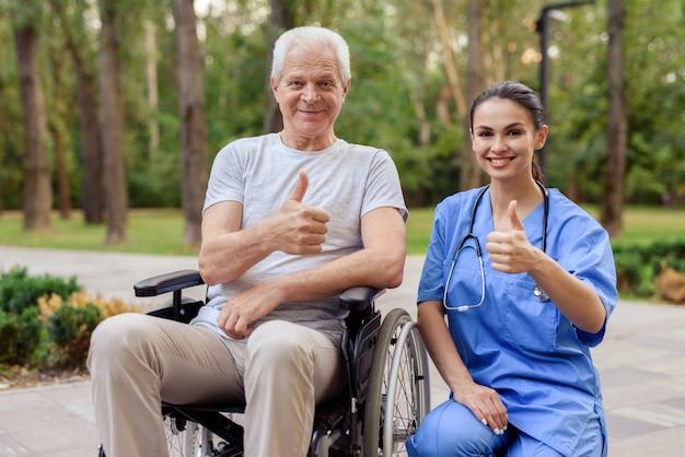Pulgares hacia arriba. el viejo que se sienta en una silla de ruedas.