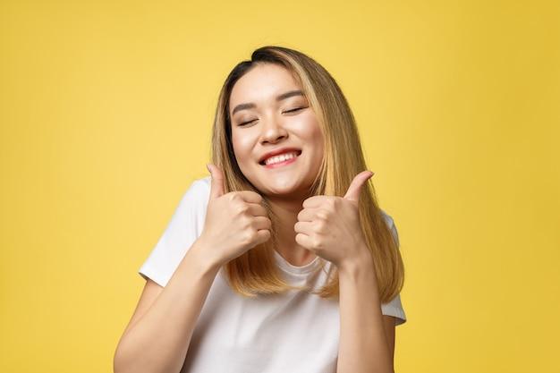Pulgares asiáticos jovenes de la demostración de la mujer para arriba en fondo amarillo
