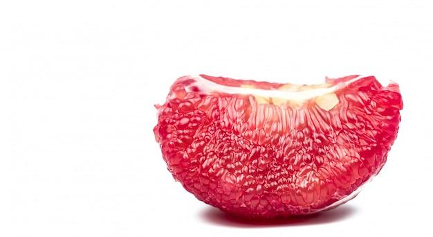 Pulpa de pomelo rojo con semillas aisladas sobre fondo blanco con trazado de recorte