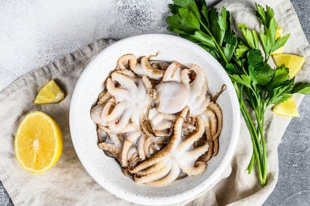 Pulpo crudo con perejil y limón en un tazón blanco. mariscos organicos. fondo gris vista superior