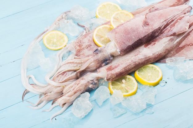 Pulpo fresco o calamares crudos sobre tabla de madera con ingredientes