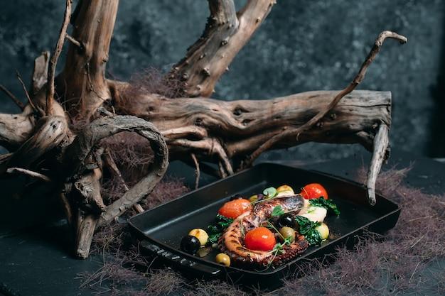 Pulpo a la plancha con tomates, aceitunas y hierbas sobre un fondo elegante