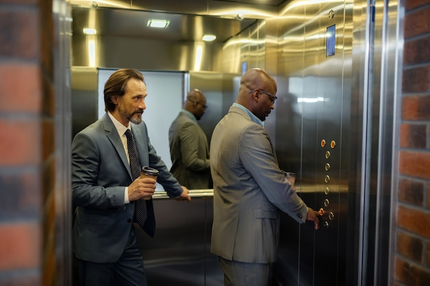 Pulsando el botón. hombre de piel oscura presionando el botón en el ascensor mientras está de pie cerca de un colega en la mañana