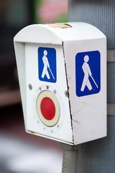 Pulsando el botón de la persona con discapacidad para cruzar la calle en el semáforo