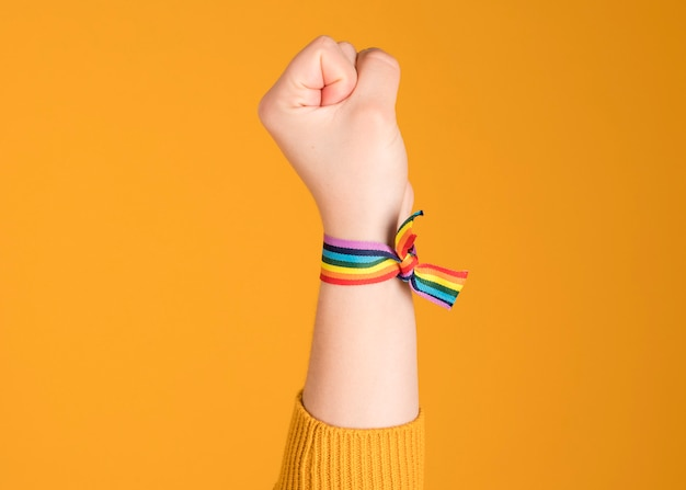 Pulsera arcoiris levantada a mano, lgbt, orgullo gay, sobre fondo amarillo pastel