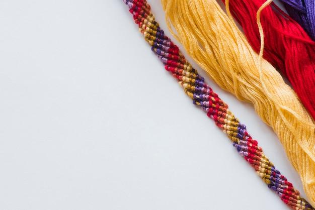 Pulsera de colores e hilos en superficie blanca.