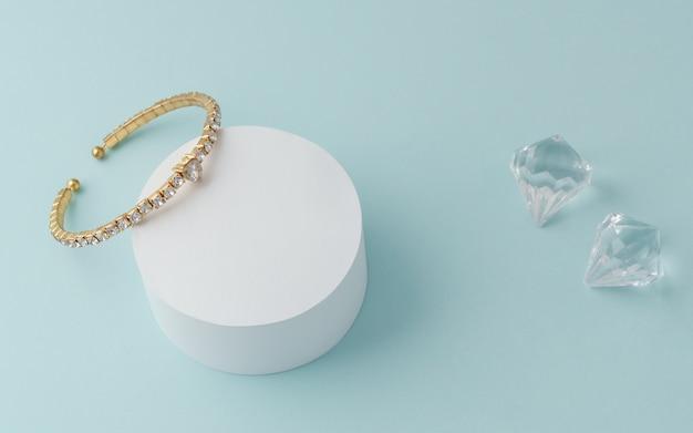 Pulsera dorada con diamantes y brillantes en la pared azul.