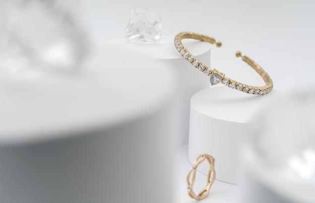 Pulsera dorada con diamantes entre diamantes sobre plataforma blanca