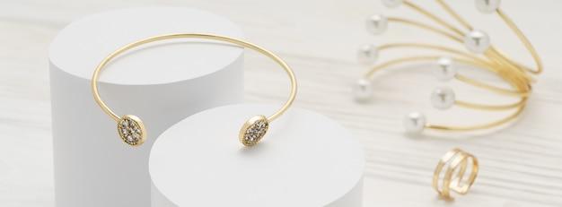 Pulsera dorada con diamantes en plataformas blancas y pulsera y anillo de perlas doradas