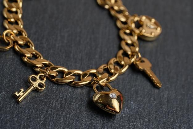Pulsera dorada con llaves y corazón.