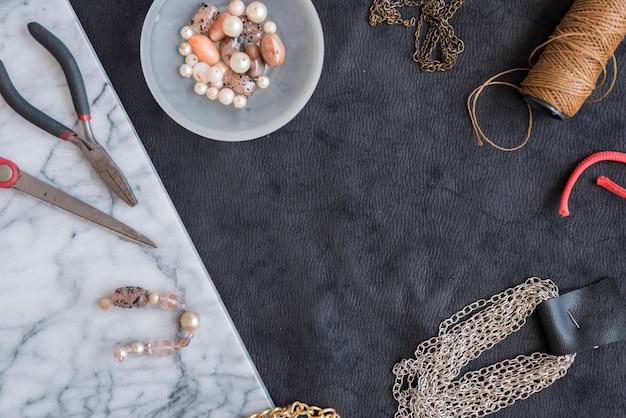 Pulsera hecha con las cuentas; cadena; carrete de hilo; alicate y tijera sobre fondo texturizado