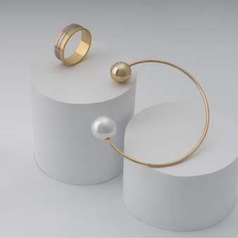 Pulsera de perlas doradas y tres tipos de anillos de oro en cilindros de papel blanco.