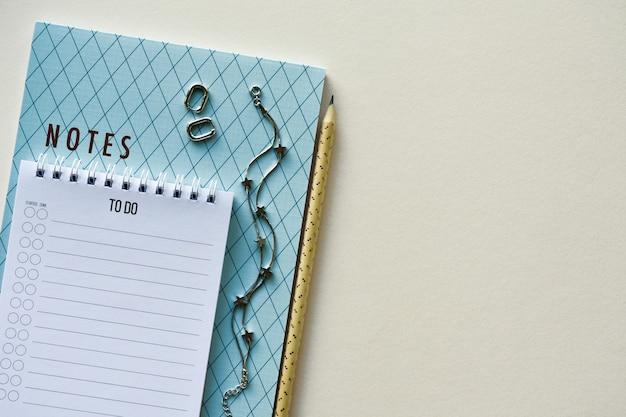 Pulsera de plata y pendientes en el bloc de notas sobre un papel beige