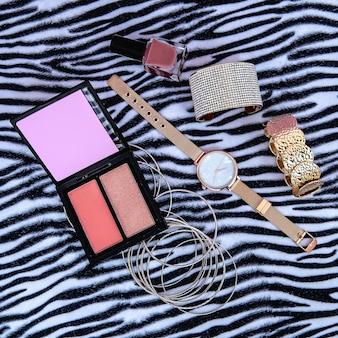 Pulseras de accesorios de muñeca y relojes sobre fondo animal. concepto de moda glam. maquillaje de moda