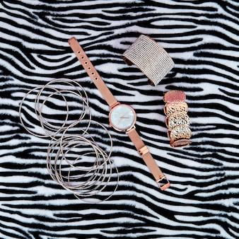 Pulseras de accesorios de muñeca y relojes sobre fondo animal. concepto de moda glam