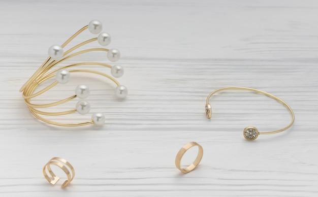 Pulseras y anillos de perlas doradas y diamantes dorados sobre superficie de madera blanca
