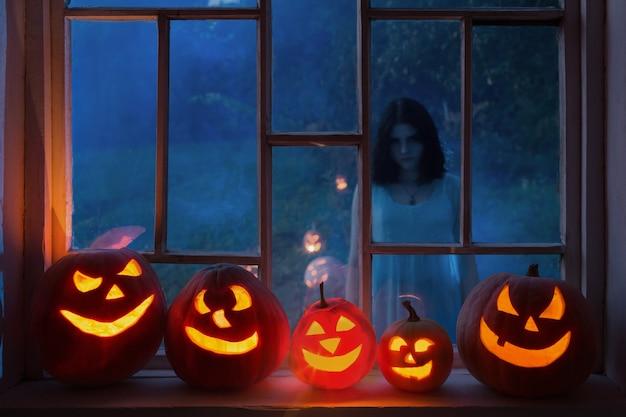 Pumpins de halloween en el alféizar de la ventana con el fantasma de la ventana exterior