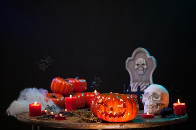 Pumpking aterrador tallado sentado en una mesa de madera con una calavera espeluznante en la celebración de halloween. decoración de halloween.