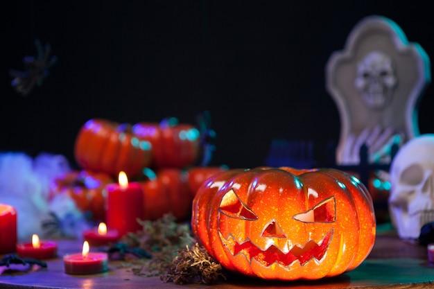 Pumpking naranja embrujado en la celebración de halloween. pequeñas calabazas al fondo. decoración de halloween.