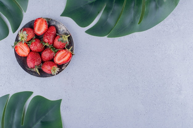Puñado de fresas y hojas decorativas sobre fondo de mármol. foto de alta calidad