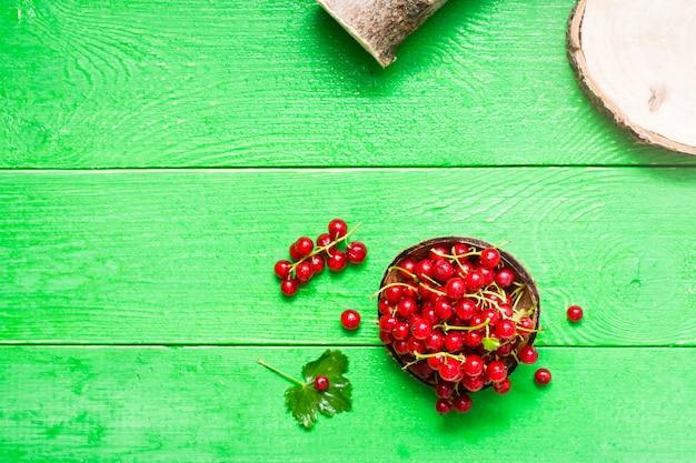Un puñado de grosellas rojas frescas en un recipiente sobre una mesa de madera verde.