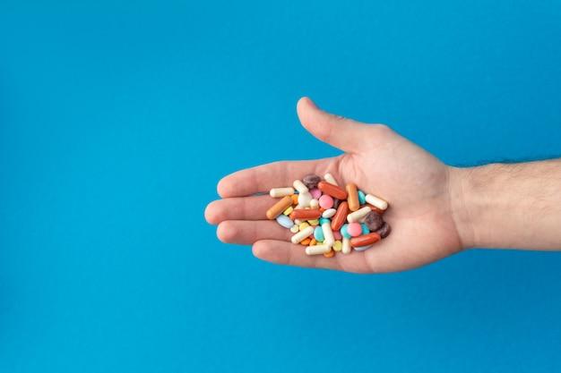 Un puñado de pastillas de colores en la palma. concepto médico compras en la farmacia.