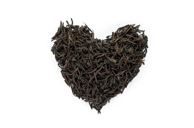 Puñado de té negro seco en forma de corazón.