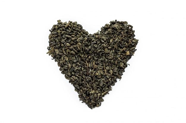 Puñado de té verde seco en forma de corazón.