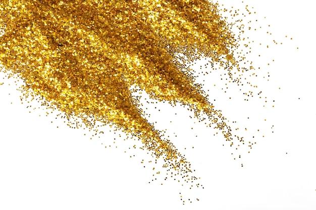 Puñado de textura de arena de brillo dorado extendido sobre fondo blanco, abstracto con espacio de copia.