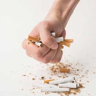 El puño del hombre arruga los cigarrillos sobre un fondo blanco
