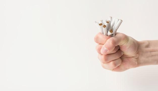 El puño del hombre que arruga los cigarrillos aislados en el fondo blanco