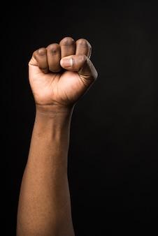 Puño levantado de un hombre negro, en actitud de lucha. sobre fondo negro.