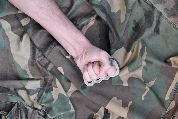 Puño masculino con nudillos de bronce en la pared de una chaqueta de camuflaje. el concepto de cultura skinhead, armas cuerpo a cuerpo hechas a mano