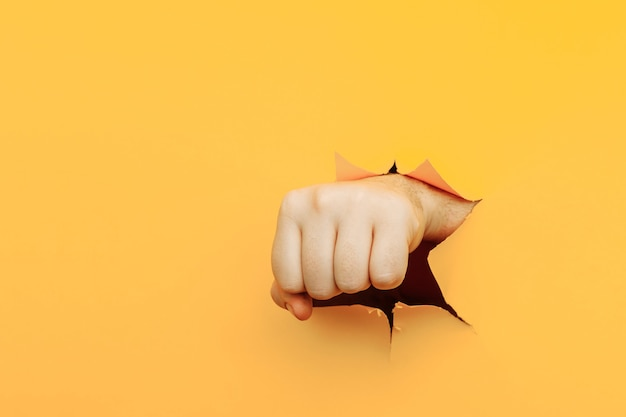 Puño perforado a través de papel amarillo fondo amenaza lucha y deportes de combate