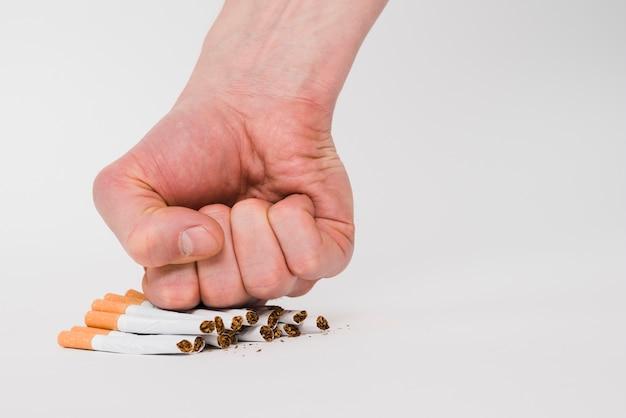 Un puño persona aplastando cigarrillos aislados sobre fondo blanco